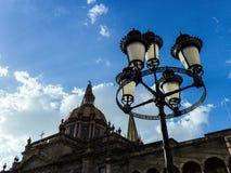 Lámpara de calle, catedral, cielo y nubes en la puesta del sol imagenes de archivo
