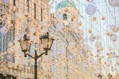 Lámpara de calle entre las luces de la Navidad imagen de archivo