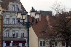 Lámpara de calle forjada hermosa grande con cuatro lámparas en el fondo de un edificio hermoso imagenes de archivo
