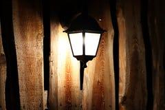 Lámpara de calle que brilla intensamente en el fondo de una cerca de madera en la noche La luz impregna la oscuridad Alumbrado pú imágenes de archivo libres de regalías
