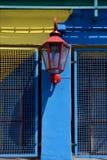 lámpara de calle roja y una pared azul amarilla en boca del la Foto de archivo libre de regalías