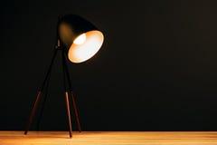 Lámpara de escritorio en la tabla en oficina oscura Imagen de archivo libre de regalías