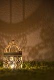 Lámpara de escritorio que brilla en una pared oscura Foto de archivo