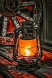 Lámpara de keroseno contra la rueda de carro del fondo Fotografía de archivo