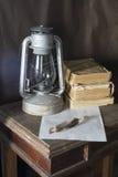 Lámpara de keroseno del envejecimiento con el libro y la pluma a descansar sobre TA de madera Foto de archivo libre de regalías