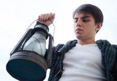 Lámpara de keroseno un hombre joven con en su mano contra el cielo foto de archivo