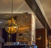 Lámpara de la bola de cristal, pared de ladrillo roja en un café acogedor Fotos de archivo