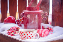 Lámpara de la vela del vintage con el corazón, taza caliente de té en la nieve Foto de archivo