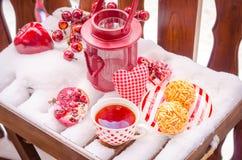 Lámpara de la vela del vintage con el corazón, taza caliente de té en la nieve Foto de archivo libre de regalías