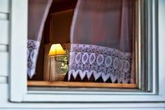 Lámpara de lectura antigua vista a través de una ventana con soplar de las cortinas foto de archivo
