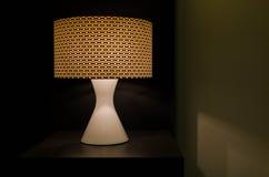 Lámpara de mesa moderna en la iluminación de la tabla en la oscuridad Foto de archivo