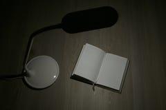 Lámpara de mesa y cuaderno abierto Foto de archivo libre de regalías
