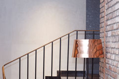 Lámpara de pie de cobre amarillo al lado de una pared de ladrillo cerca de las escaleras imagen de archivo libre de regalías