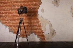 Lámpara de pie pasada de moda en el trípode cerca de la pared de ladrillo foto de archivo libre de regalías