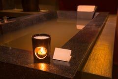 Lámpara del aroma con la vela ardiente en cuarto de baño Fotos de archivo libres de regalías