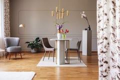 Lámpara del oro sobre la mesa de comedor y sillas en interior gris del apartamento con las flores y la butaca Foto verdadera foto de archivo libre de regalías