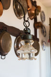 Lámpara del vintage en la pared del fondo con los utensilios de cobre antiguos foto de archivo