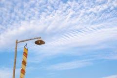 Lámpara del vintage encima del polo de bambú y flagTung amarillo del lanna en el cielo azul por la mañana imagenes de archivo