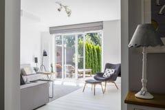 Lámpara en el gabinete y ventanas en el interior blanco de la sala de estar con g foto de archivo libre de regalías