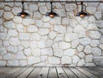 Lámpara en la pared de piedra en el sitio de madera del piso Imágenes de archivo libres de regalías