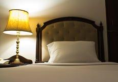 Lámpara en una tabla de noche al lado de una cama Fotografía de archivo libre de regalías