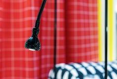 Lámpara flexible negra en un fondo de cortinas a cuadros rojas fotos de archivo