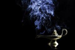 Lámpara mágica de la historia de Aladdin con los genios que aparecen en el concepto azul del humo para desear, la suerte y la mag imagenes de archivo