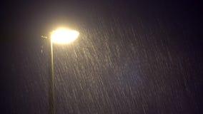 Lámpara pública iluminada en fuertes lluvias oscuras de la noche almacen de metraje de vídeo
