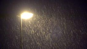 Lámpara pública iluminada en fuertes lluvias oscuras de la noche metrajes