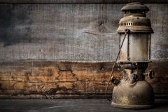 Lámpara pasada de moda de la linterna del aceite del keroseno del vintage que quema con una luz suave del resplandor con el piso  Foto de archivo