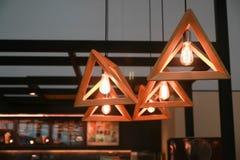 Lámpara pendiente del triángulo de madera en cafetería fotos de archivo