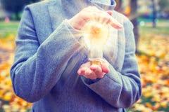 Lámpara que brilla intensamente a disposición de la mujer joven en primer del parque del otoño Idea, concepto fresco del pensamie foto de archivo