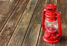 Lámpara roja del vintage en la tabla de madera. copie el espacio. fotos de archivo libres de regalías