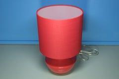 Lámpara roja en gris de la textura de la tabla y azul del blackground Fotos de archivo libres de regalías