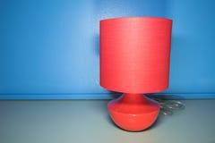 Lámpara roja en gris de la textura de la tabla y azul del blackground Imagenes de archivo
