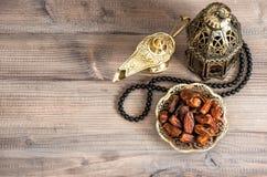 Lámpara, rosario y fechas del Ramadán en fondo de madera Foto de archivo libre de regalías