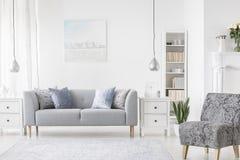 Lámpara sobre el gabinete blanco entre la planta y el sofá gris en interior plano simple con la butaca Foto verdadera imagen de archivo libre de regalías