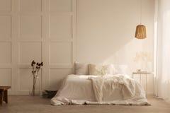 Lámpara sobre la cama blanca con las almohadas en interior mínimo del dormitorio con las plantas y el taburete imagenes de archivo