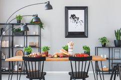Lámpara sobre sillas negras y tabla de madera con la comida en el comedor gris interior con el cartel imagen de archivo libre de regalías