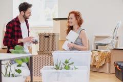 Lámpara sonriente del embalaje de la mujer en las cajas durante la relocalización al nuevo hogar con el marido imagen de archivo