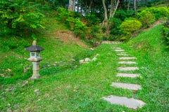 Lámpara tradicional asiática en un jardín con camino enorme del césped y de la piedra Imagenes de archivo