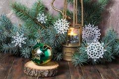 Lámpara vieja con la vela, la bola de la Navidad y el árbol de navidad ardientes Foto de archivo libre de regalías