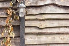 Lámpara vieja del vintage en la cerca de madera foto de archivo