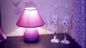 Lámpara y dos vidrios en la tabla en el dormitorio almacen de video