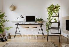 Lámpara y equipo de escritorio en el escritorio negro en los wi interiores del espacio de trabajo Fotos de archivo