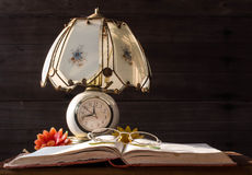 Lámpara y libros viejos con los vidrios de lectura Fotografía de archivo