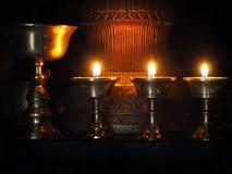 Lámparas de aceite tibetanas piadosas del metal antiguo grande con las luces en el cuarto oscuro del monasterio budista Imagen de archivo libre de regalías