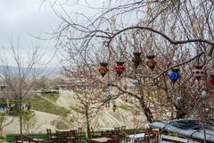 Lámparas multicoloras turcas tradicionales en las ramas de un árbol Primavera temprana, preparación para la estación turística en fotografía de archivo