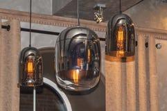 Lámparas pendientes modernas, con las lámparas eléctricas encendido, contra una cortina, techo imágenes de archivo libres de regalías