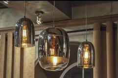 Lámparas pendientes modernas, con las lámparas eléctricas encendido, contra una cortina, techo foto de archivo